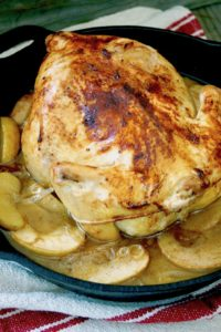 Whole roasted chicken surrounded by apples slices in a cast iron skillet.