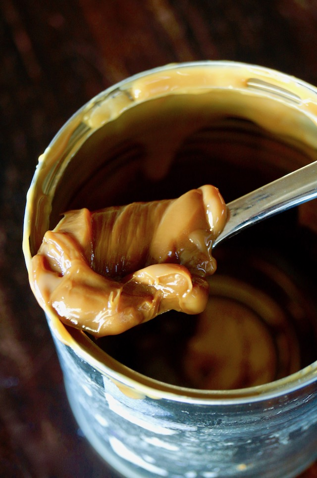Spooonfull of homemade dulce de leche resting on the rim of a can.