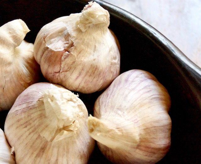 a few heads of purplish garlic in black bowl.