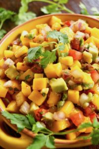 Mango Avocado Chipotle Salsa in a yellow bowl with fresh cilantro