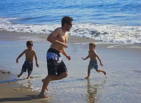 Valentina's husband and kids at the beach running around
