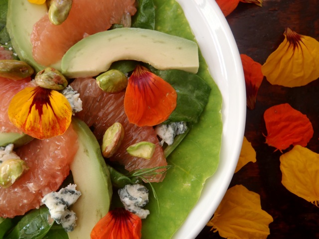 Grapefruit-Avocado Salad on a white plate with orange and yellow flower petals