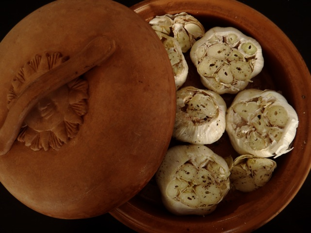 six heads of garlic with tops cut off in terracotta dish for roasting
