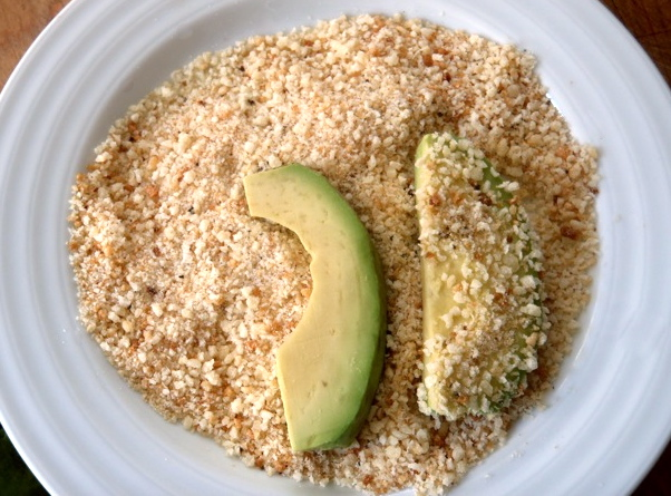two slices of avocado being dipped into breadcrumbs