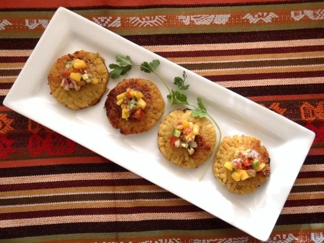 four Plantain-Picadillo Empenadas with Mango Salsa on a white rectangular dish