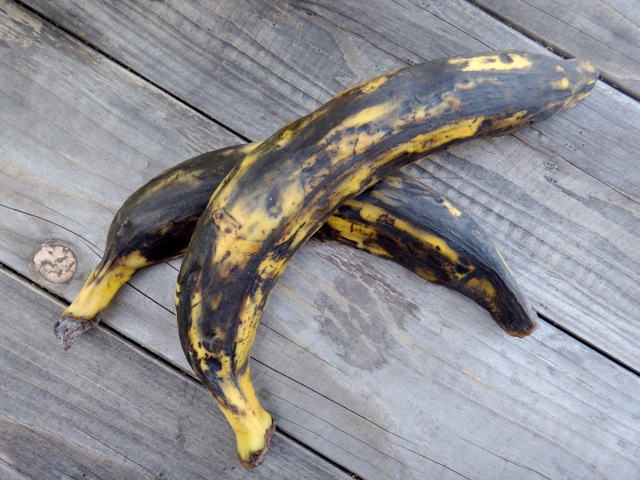 two fully ripe plantains on a wooden table