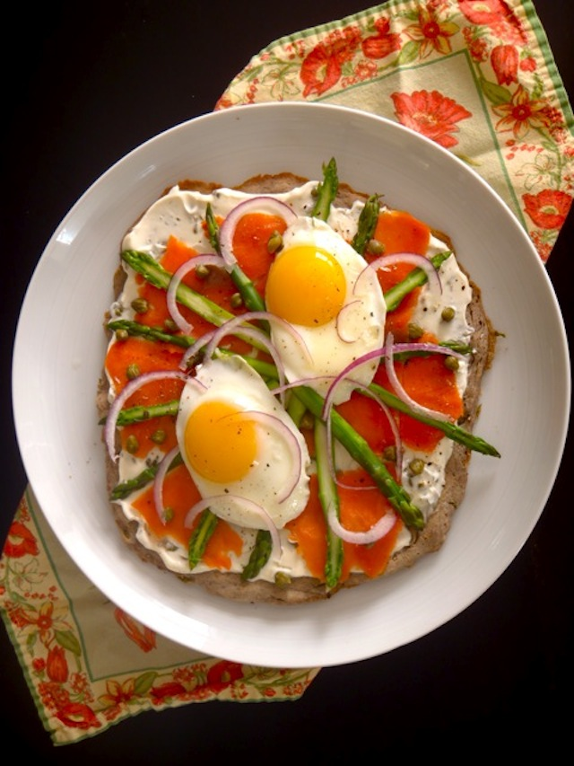 Smoked Salmon-Asparagus Breakfast Pizza on a white plate with two sunny side up eggs