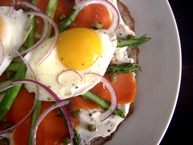 Smoked Salmon-Asparagus Breakfast Pizza on a white plate with sunny side up egg