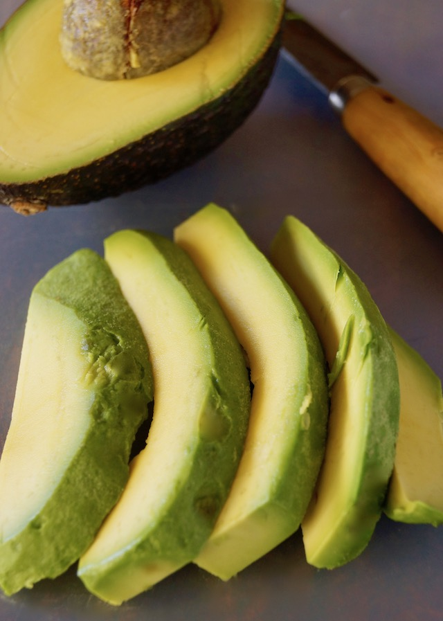 A few thick slices of avocado and half an avocado with pit