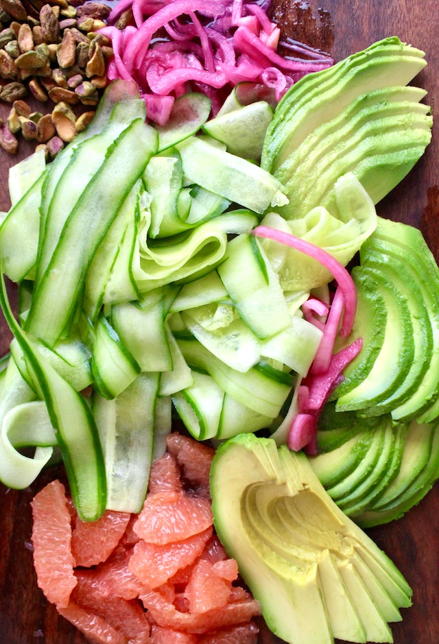 cucumber, grapefruit, pistachios, red onion and avocados on wood cutting board