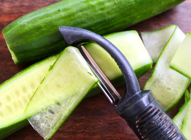 Cucumber being slices with a vegetable peeler