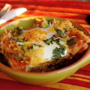 Smoky Chipotle Breakfast Nachos in a light green bowl on a red and brown striped cloth.