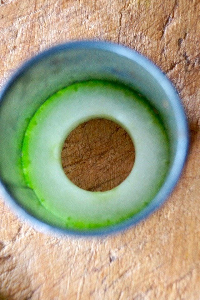 Top view of a round cutter around a cucumber slice, to cut off the skin.