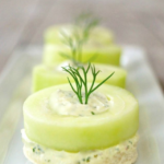 Row of Cucumber Dill Canapes on a white, narrow plate.