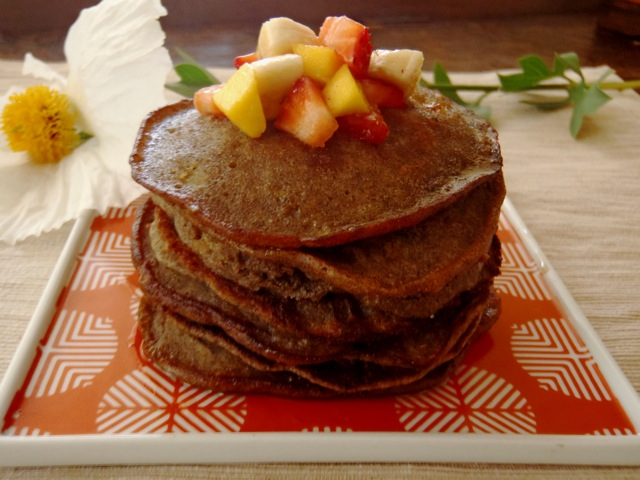Gluten-Free Buckwheat Pancakes on a red square plate with fresh fruit on top