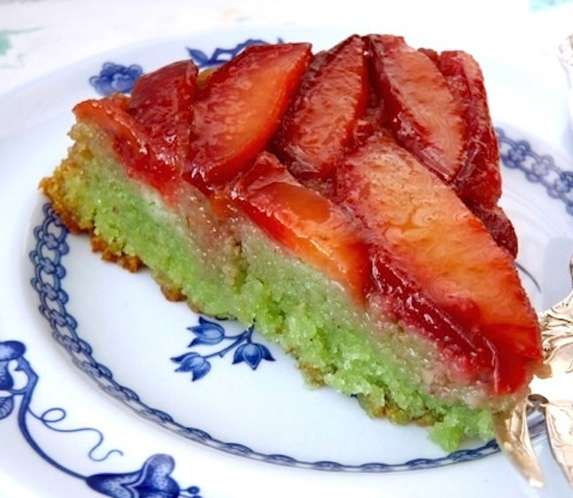 one slice of Almond-Plum Upside Down Cake with Pandan on a white plate with blue flowers