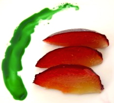 streak of pandan and three red plum slices on white background