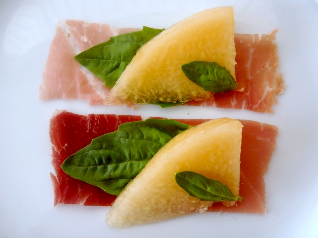 Prosciutto and Kiss melon with basil leaves