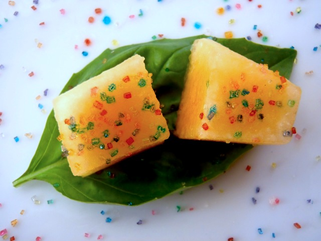 two squares of kiss melon on a basil leaf with sprinkles of colored sugar