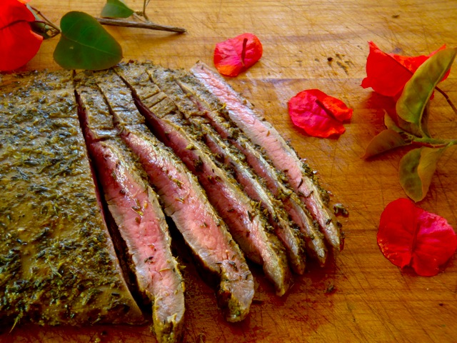 Grilled Mediterranean Marinated Steak sliced on a cutting board