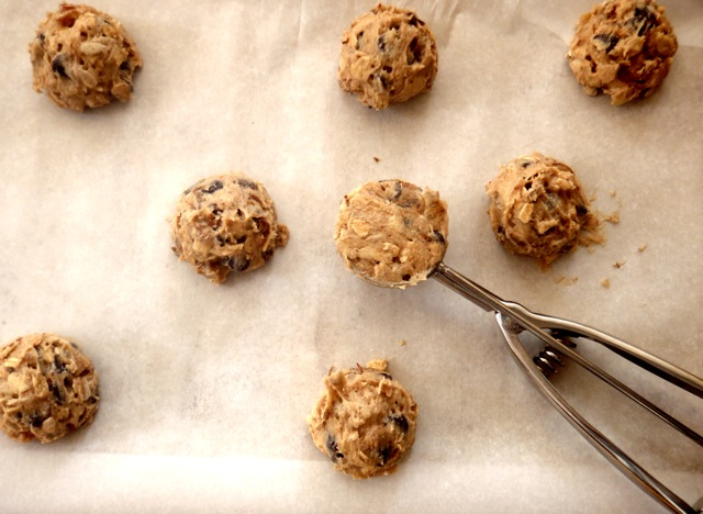 Granola Chocolate Chip Cookie batter being shaped into balls and placed on a baking sheet with parchment