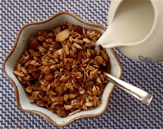 Father's Day apple spiced granola in a cream-colored bowl with milk being poured into it