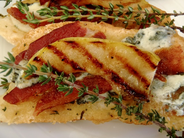 Roasted Garlic Bread Recipe with Roquefort, Bacon and Grilled Pear on a white plate with fresh sprigs of theyme