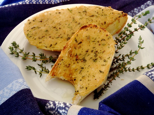 Roasted Garlic Bread on a white plate with fresh thyme sprigs