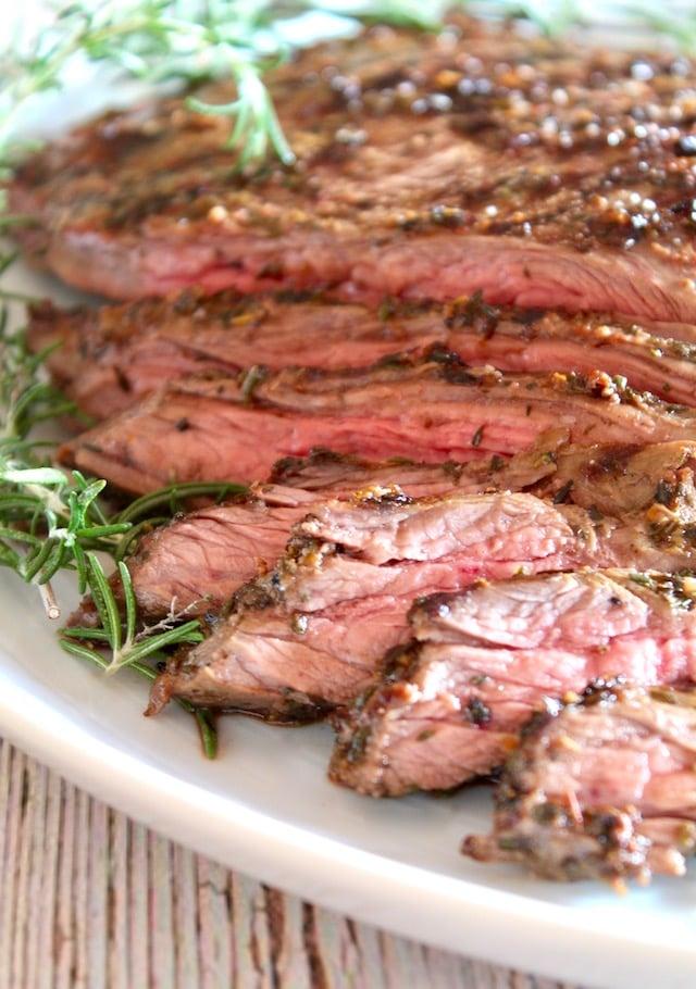 sliced mediterranean marinated steak with fresh rosemary on white platter