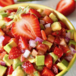 Strawberry Avocado Salsa recipe in a yellow-green bowl with half of a whole strawberry on top