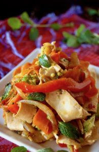 Close up of Vegetable Mint Stir Fry Recipe wtih Tofu Noodles on a square white plate, with a red cloth beneath it.