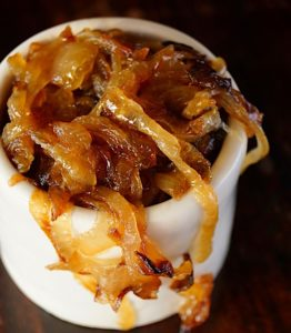 Top view of caramelized onions in a small white bowl with some hanging over the side