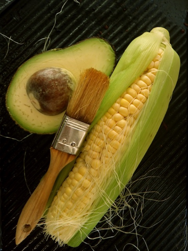 half an avocado with an ear of corn on a grill