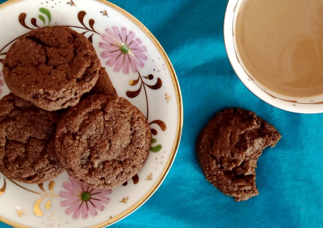 larger Double Chocolate Almond Spice Cookies on a pretty floral a cup of coffeeplate with