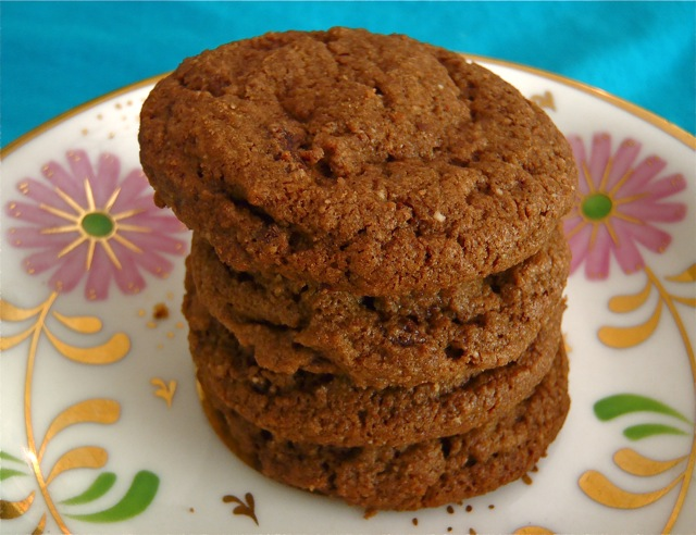 Stack of 4 Double Chocolate Almond Spice Cookies on a gold-rimmed -plate with pink flowers.