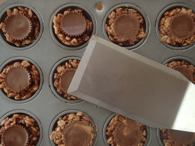 rice krispie treats with a Reeses peanut butter cup in the center of each one, in a small muffin tin pan