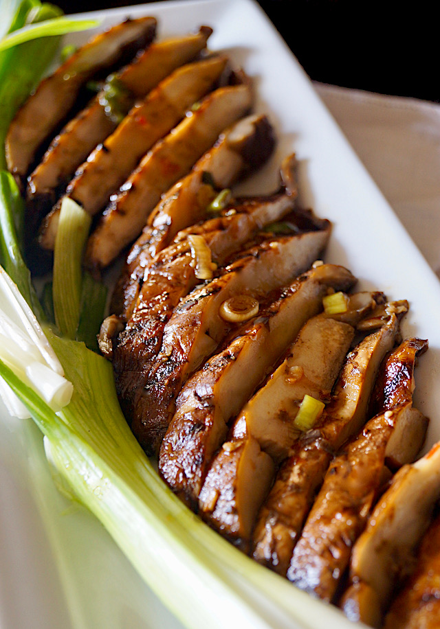 Close up of sliced Sliced Marinated Grilled Portabello Mushrooms on a white rectangulsr plate with green onions.