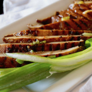 Sliced Marinated Grilled Portabello Mushrooms on a white plate with green onions.