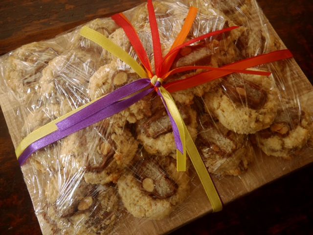 gluten-free almond joy cookies wrapped as a gift on a cutting board with pretty colored ribbons