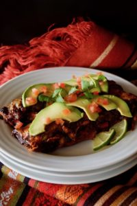 2 of the best vegetarian enchiladas ever, on a white plate, topped with thin avocado slices and diced tomatoes.