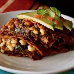 Vegetarian enchilada, cut in half on a white plate with avocado slices and diced tomato on top.