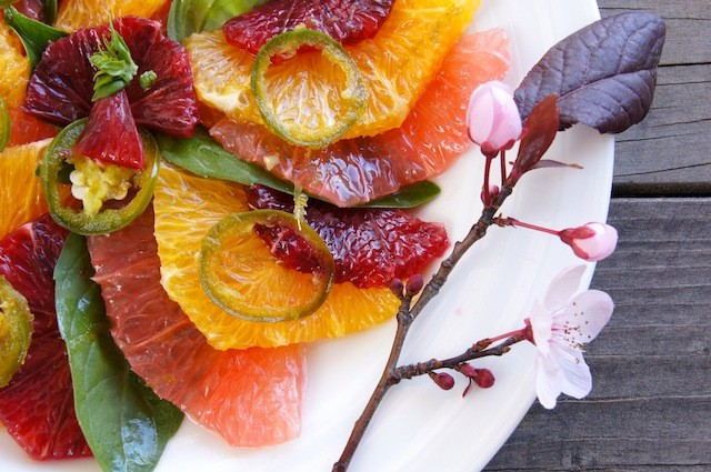 Thinly sliced citrus on a white plate with pink flowers