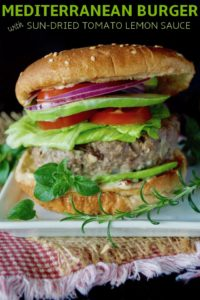 Grilled Mediterranean Burger in a bun with tomato, lettuce, onion and avocado.