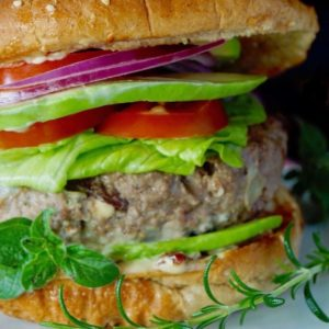 Close up of a Grilled Mediterranean Burger in a bun with all the fixins.