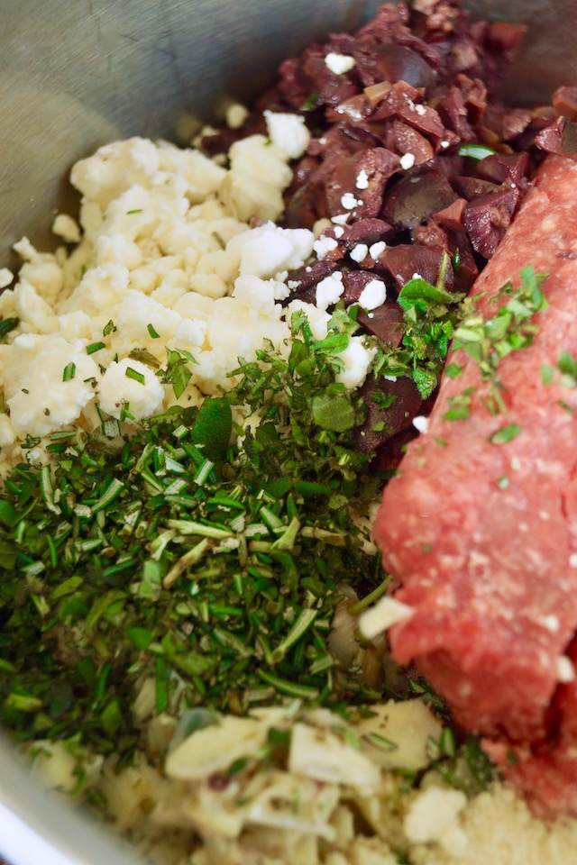 Bowl of ingredients for Grilled Mediterranean Burgers with chopped herbs on top.