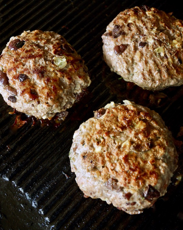 Three Grilled Mediterranean Burgers on the grill.