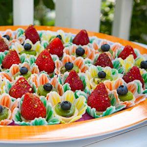 about a dozen bite-sized fruit tarts on orange-rimmed plate