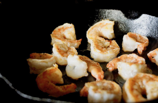 Several cooked shrimp in a cast iron skillet
