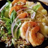Tropical Quinoa Salad Bowl with Shrimp in a dark ceramic bowl on a sushi mat