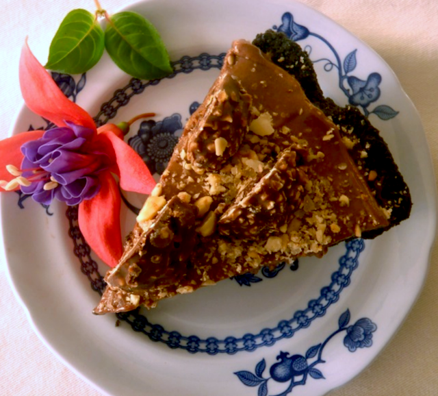 top view of hazelnut praline nutella pie on white and blue plate with flower